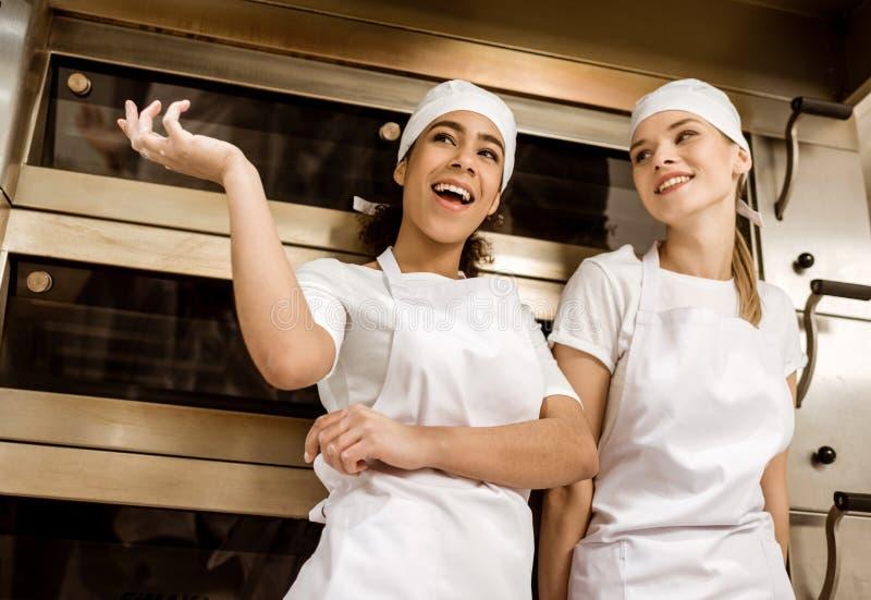 het gelukkige vrouwelijke bakkers babbelen stock afbeelding