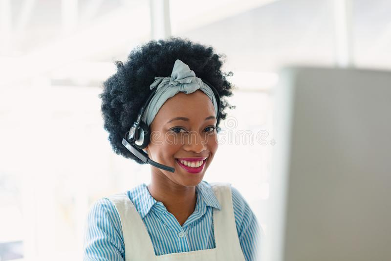 Het gelukkige vrouwelijke klantenservice uitvoerende spreken op hoofdtelefoon in bureau stock foto's