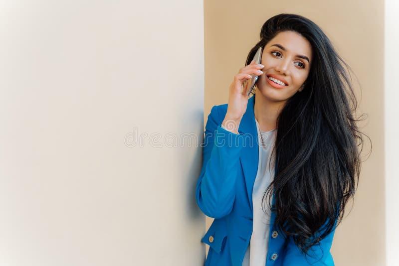 Het gelukkige vrouwelijke model met donkere lange haarvraag via celtelefoon en spreekt in het zwerven draagt matroos kijkt heeft  royalty-vrije stock foto's