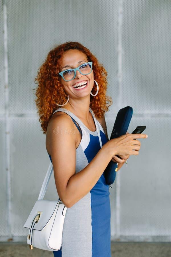 Het gelukkige vrouwelijke ondernemer texting op smartphone buiten stock foto's