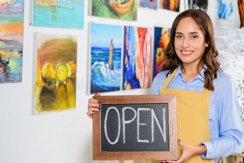 het gelukkige vrouwelijke uithangbord van de kunstenaarsholding met open woord royalty-vrije stock afbeelding