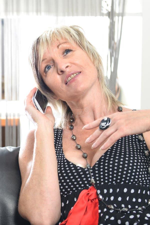 Het gelukkige vrouwentelefoon spreken Gezicht met toothy glimlach stock foto