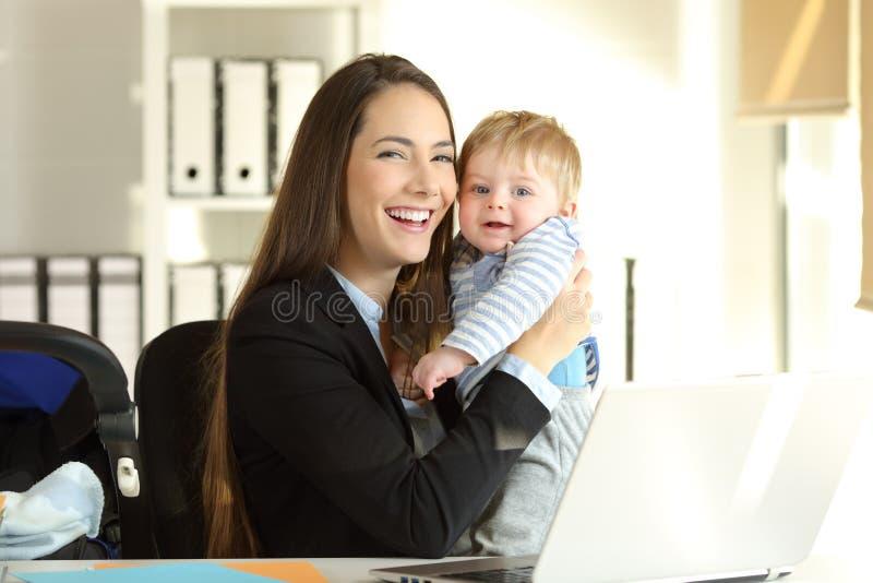 Het gelukkige het werk moeder stellen met haar baby op kantoor royalty-vrije stock fotografie