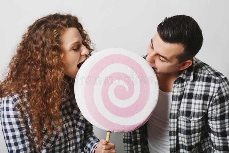 Het gelukkige wijfje en het mannetje hebben pret samen, beet de grote ronde lolly, van snoepjes dat houdt, over witte achtergrond stock foto's