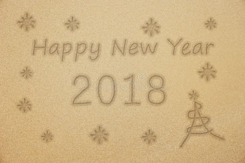 Het gelukkige woord van het Nieuwjaar 2018 handschrift met Kerstmisboom en op fijn zand stock fotografie