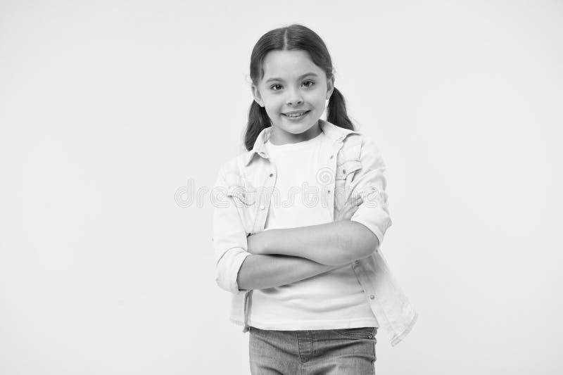 Het gelukkige zekere die kind houdt wapens op Vrolijk en zekere borst worden gekruist Meisje met leuke glimlach Toevallig kijk en stock afbeelding