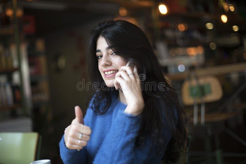 Het gelukkige zekere mooie vrouw gesturing beduimelt omhoog het bekijken camerazitting in een koffie terwijl het roepen telefonis stock foto's
