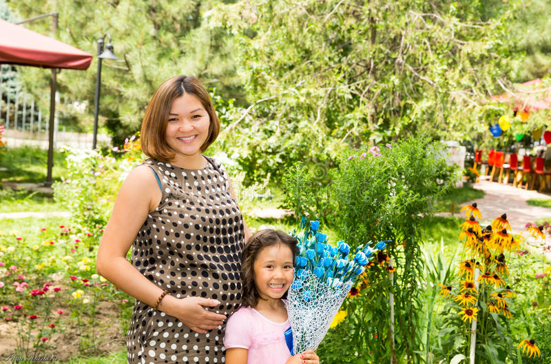 Het gelukkige zwangere Aziatische mamma en kindmeisje koesteren Het concept kinderjaren en familie royalty-vrije stock foto's