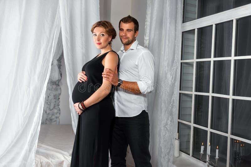 Het gelukkige Zwangere Paar gekleed in zwarte omhelst elkaar door het venster stock foto's