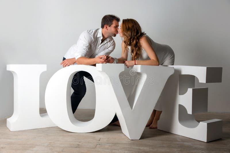 Het gelukkige Zwangere Paar kleedde zich in het witte kussen op witte achtergrond met reuze met de hand gemaakte brieven van de w royalty-vrije stock fotografie