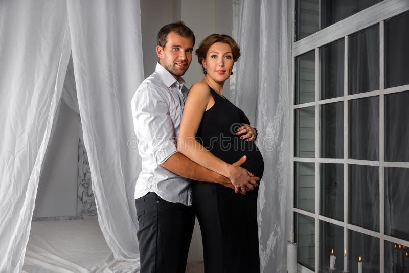 Het gelukkige Zwangere Paar kleedde in zwart-witte greep elkaar door het venster stock fotografie