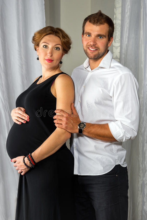 Het gelukkige Zwangere Paar kleedde in zwart-witte greep elkaar door het venster royalty-vrije stock foto