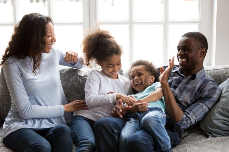 Het gelukkige zwarte familie het lachen spelen thuis kietelend kinderen stock foto's
