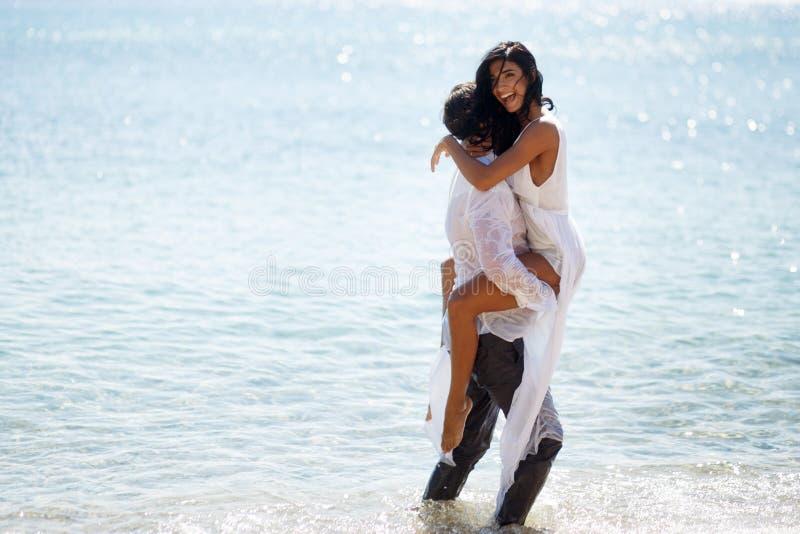 Het gelukpaar geniet van op het strand, verleidelijk beeld van gekke jonggehuwden, dat op een blauwe water Middellandse Zee wordt royalty-vrije stock foto