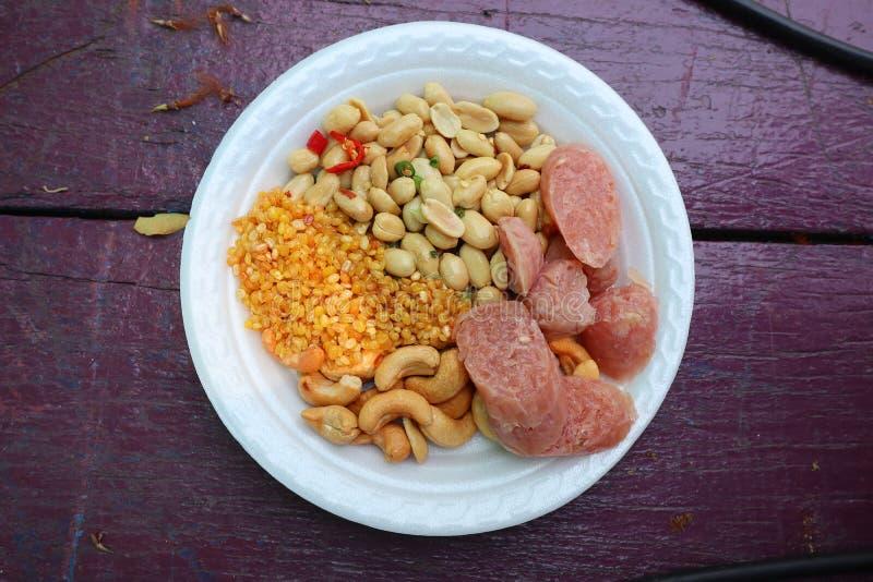 Het gemarineerde varkensvlees of Nham, Thais voedsel, braadde bonen, cashewnoten Gebraden sojabonen met witte platen, houten acht royalty-vrije stock foto's