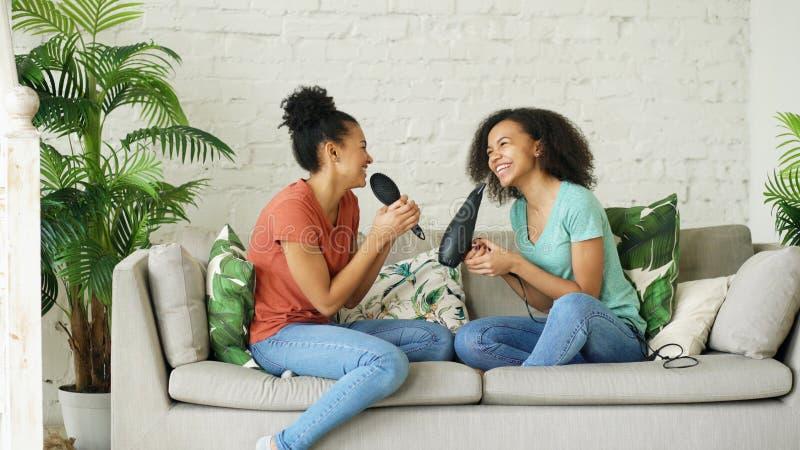 Het gemengde de dans van ras jonge grappige meisjes zingen met hairdryer en kamzitting op bank Zusters die pretvrije tijd in het  stock afbeeldingen