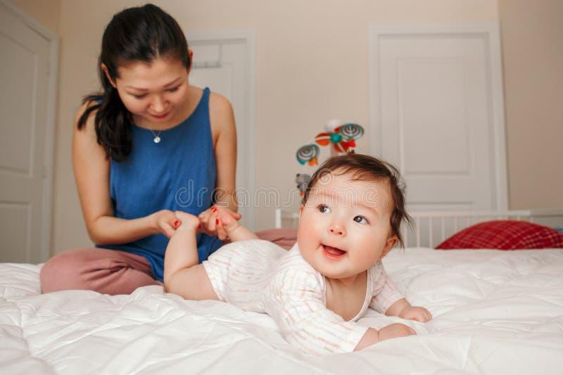 Het gemengde ras Aziatische moeder kussen wat betreft het omhelzen van haar pasgeboren zuigelingsbaby stock fotografie