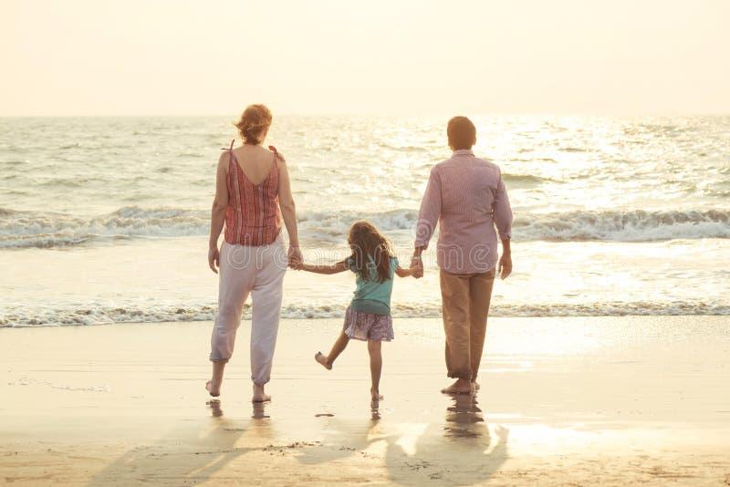 Het gemengde rasfamilie spelen met kind op overzees bij zonsondergang stock afbeeldingen