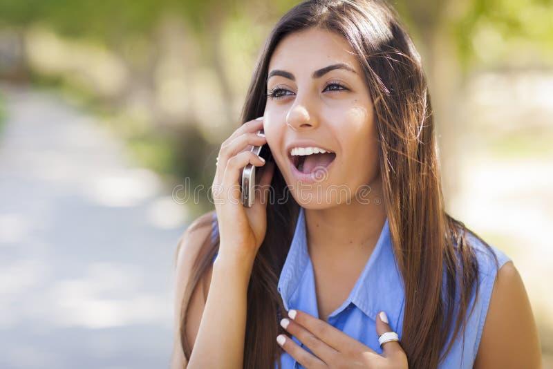 Het gemengde Wijfje die van de Ras Jonge Volwassen Tiener Haar Celtelefoon met behulp van stock foto's
