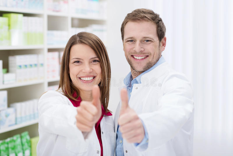 Het gemotiveerde apothekers geven duimen omhoog stock foto's
