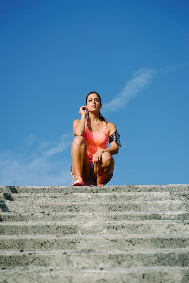 Het gemotiveerde vrouw rusten en het luisteren muziek na het beklimmen van trede royalty-vrije stock afbeelding