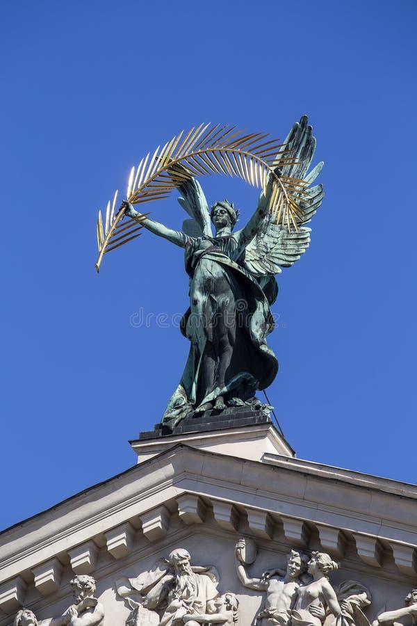 Het genie van het bronsbeeldhouwwerk met gouden palmtak en vleugels op het dak van het opera en ballettheater in Lviv, de Oekra?n stock afbeeldingen