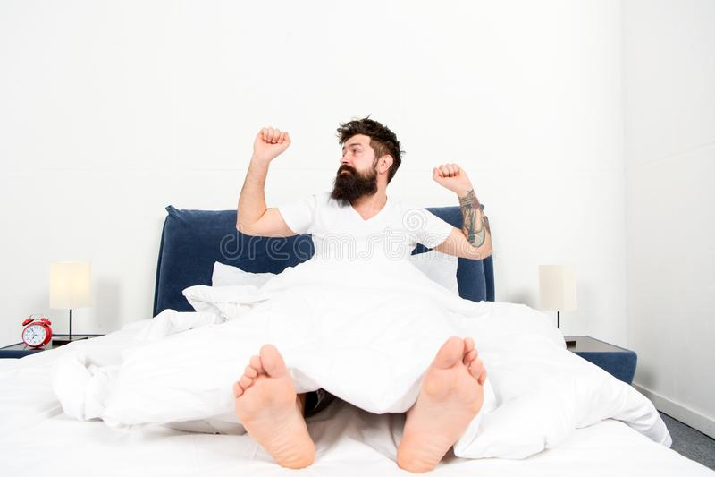 Het genieten van van aardige ochtend energie en vermoeidheid in slaap en wakker brutale slaperige mens in slaapkamer gebaarde men stock foto's