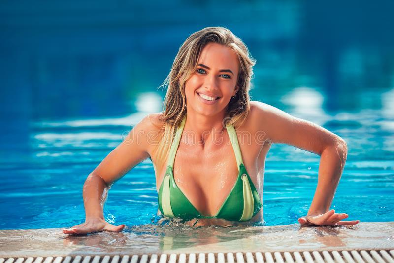 Het genieten van bruine kleur van Vrouw in bikini in het zwembad stock afbeelding