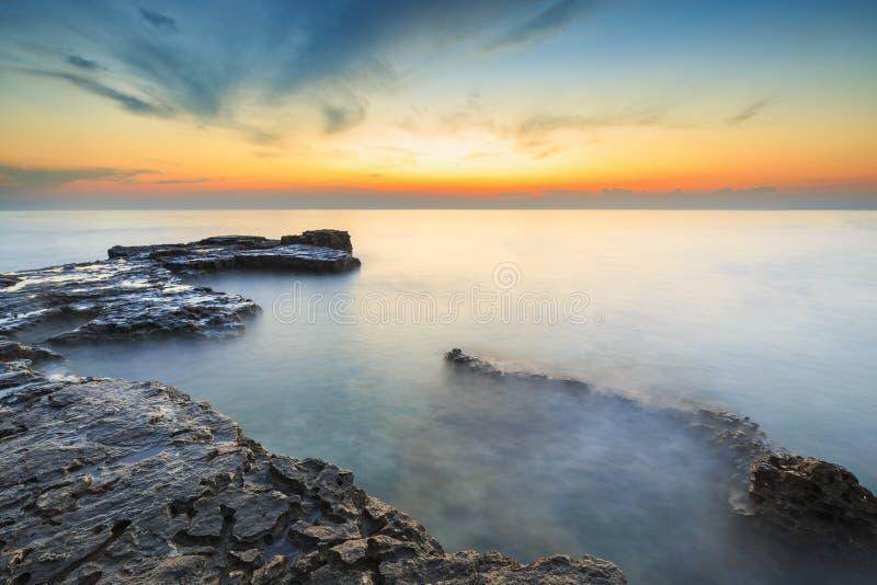 Het genieten van de van kleurrijke zonsondergang op een strand met rotsen op de Adriatische Overzeese kust Istria Kroatië royalty-vrije stock foto's