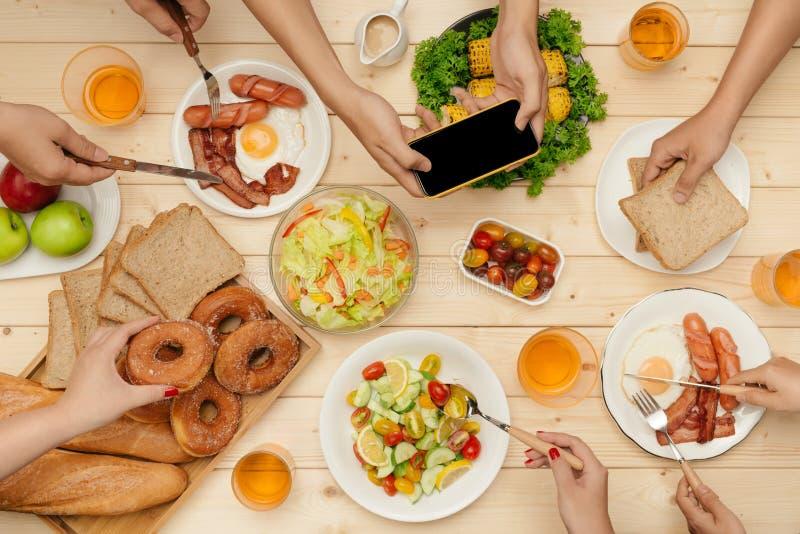 Het genieten van van diner met vrienden Hoogste mening van groep mensen die diner hebben samen terwijl het zitten bij houten lijs stock afbeeldingen