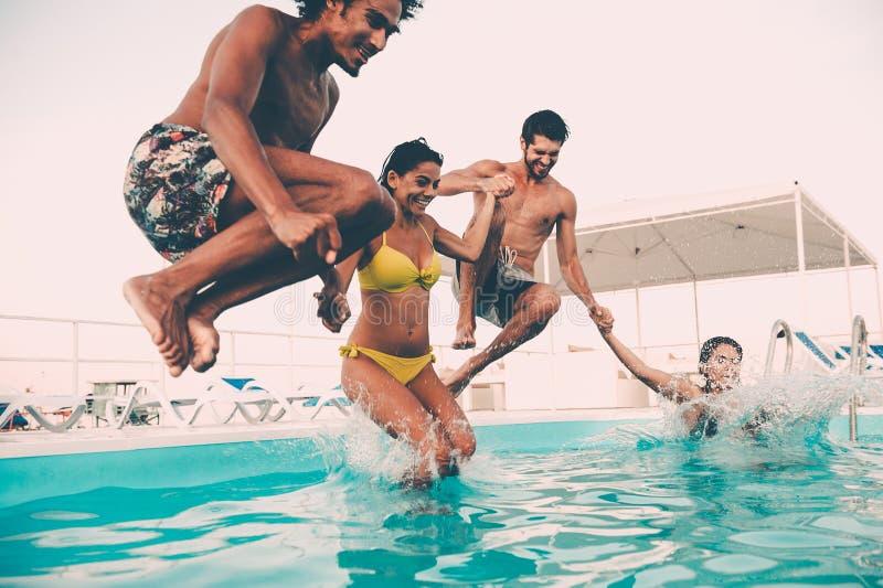 Het genieten van pool van partij met vrienden stock foto's