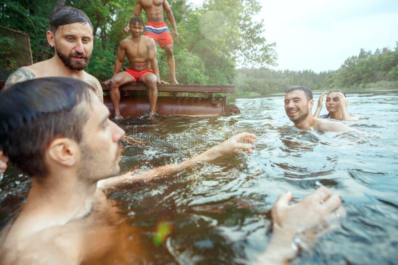 Het genieten van rivier van partij met vrienden Groep mooie gelukkige jongeren bij de rivier samen stock fotografie