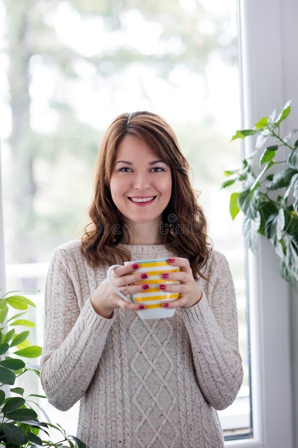 Het genieten van van thee door het venster royalty-vrije stock foto