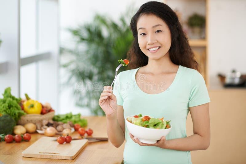 Het genieten van van verse salade royalty-vrije stock afbeelding
