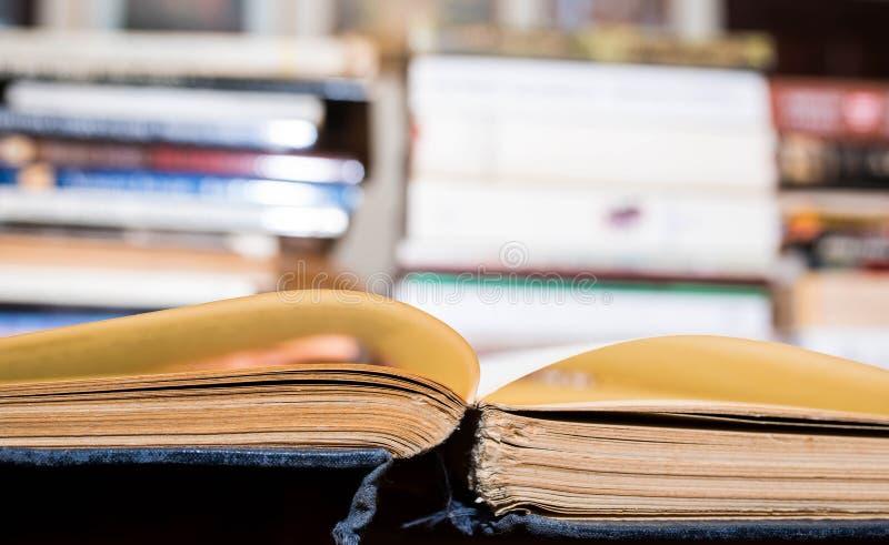 Het geopende oude boek bij de bibliotheek, boeken in rij op blured achtergrond stock afbeelding