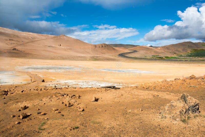 Het geothermische gebied Hverir, s-vormige weg en multicolored, barstte oppervlakte, Namafjall, IJsland stock fotografie