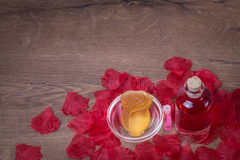 Het geparfumeerde die rozewater en nam bloem van zeep in glaswerk op houten lijst met roze bloemblaadjes wordt gemaakt toe royalty-vrije stock foto's