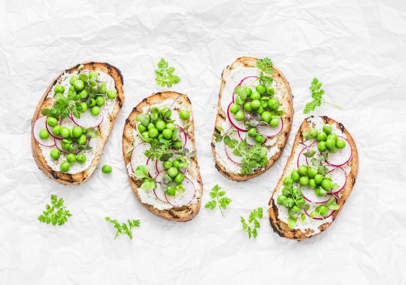 Het geroosterde brood, de zachte kaas, de groene erwten, de radijzen en de micro maken de lentesandwiches groen Het gezonde eten, stock foto's