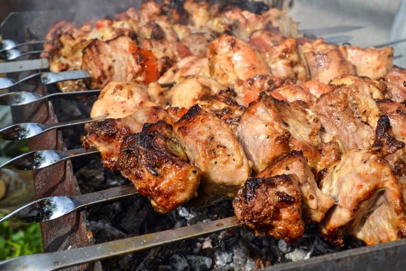 Het geroosterde kebab koken op de close-up van de metaalvleespen Geroosterd die vlees bij barbecue wordt gekookt Traditionele oos stock afbeelding
