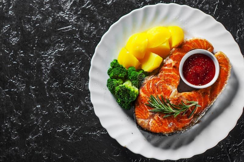 Het geroosterde lapje vlees van zalmvissen met aardappel, broccoli en saus in witte plaat royalty-vrije stock afbeelding