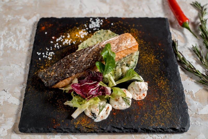 Het geroosterde lapje vlees van zalmvissen met aardappel, broccoli en saus in witte plaat op donkere achtergrond stock afbeelding