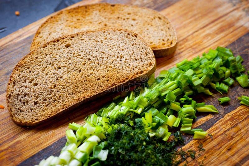 Het geroosterde roggebrood en de groene uien hakten fijn met greens op de oppervlakte van de scherpe raad royalty-vrije stock foto