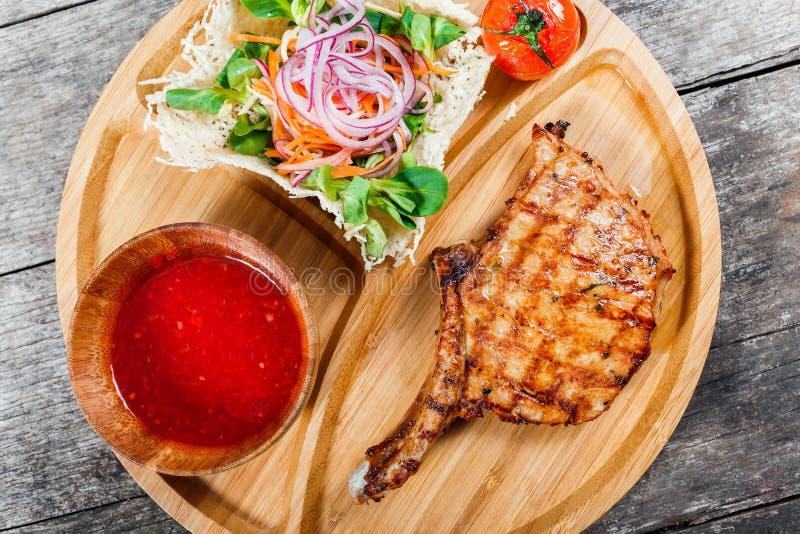 Het geroosterde rundvleeslapje vlees op been, verse salade, roosterde groenten en tomatensaus op scherpe raad op houten achtergro stock afbeelding