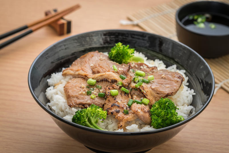 Het geroosterde varkensvlees met beweegt gebraden broccoli en Japanse rijst in kom stock foto's