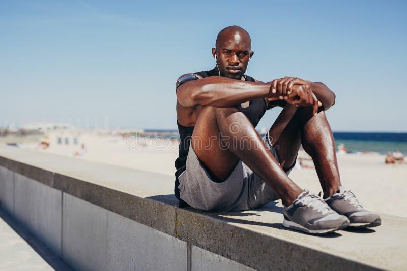 Het geschikte jonge atleet ontspannen op zeedijk na training stock foto's