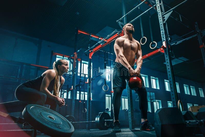 Het geschikte jonge mens het opheffen barbells uitwerken in een gymnastiek royalty-vrije stock foto