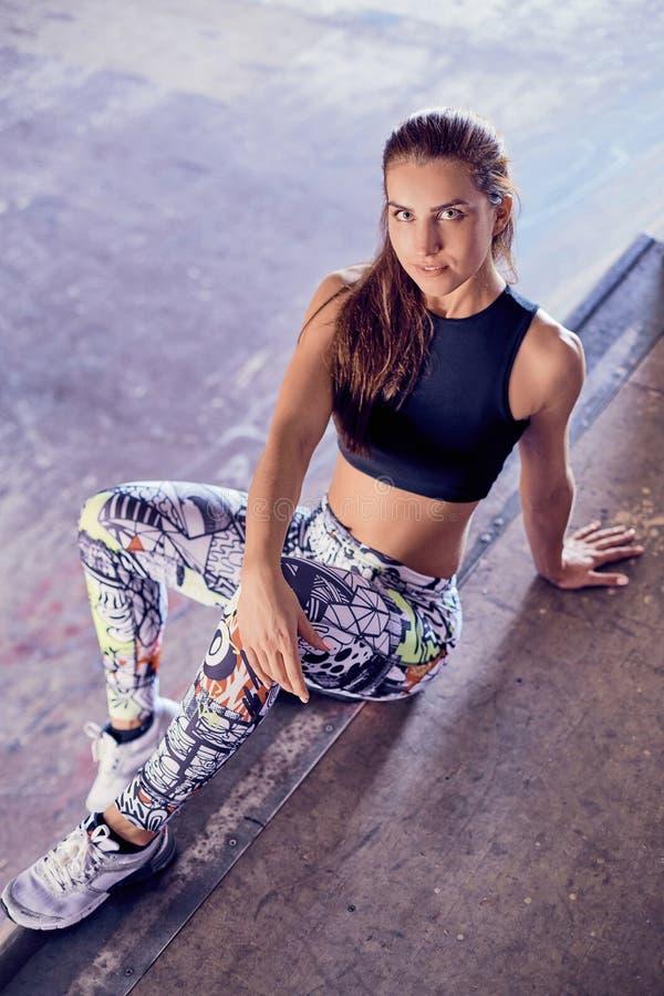 Het geschikte jonge vrouw ontspannen na oefening op de vloer stock afbeeldingen