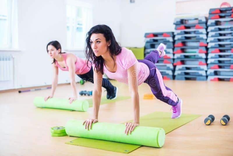Het geschikte vrouw uitrekken zich op vloer die schuimrol met behulp van die plankoefening doen stock foto