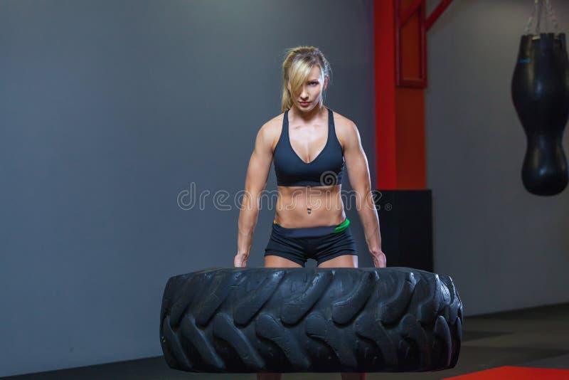 Het geschikte vrouwelijke atleet uitwerken met een reusachtige band, draaiend en draagt in de gymnastiek Crossfitvrouw die met gr royalty-vrije stock fotografie