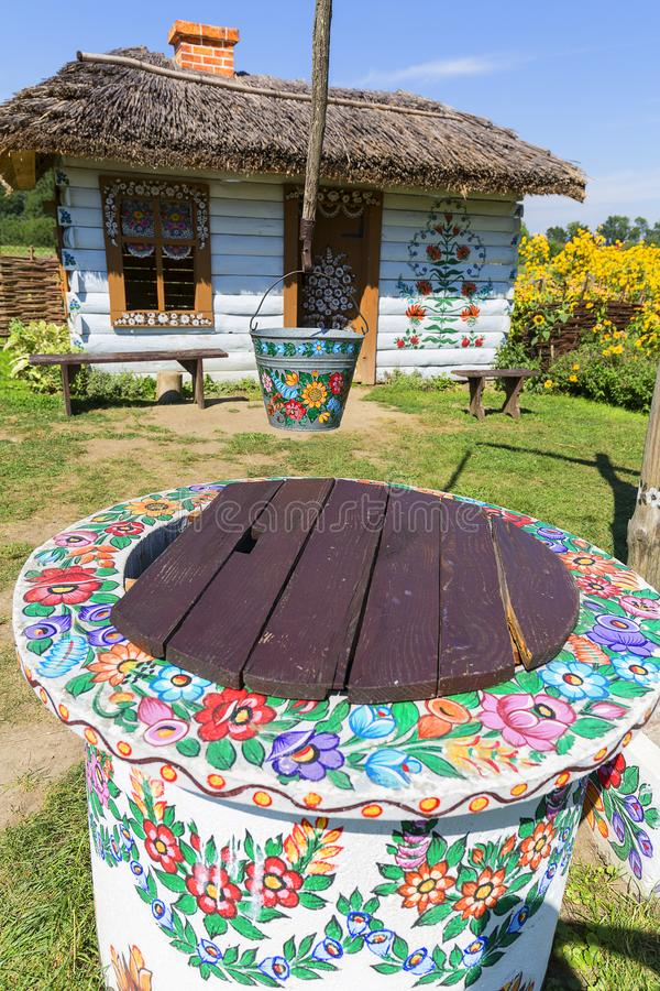 Het geschilderde oude houten die plattelandshuisje, goed en emmer, met een geschilderde hand wordt de verfraaid bloeien, Zalipie, royalty-vrije stock foto's